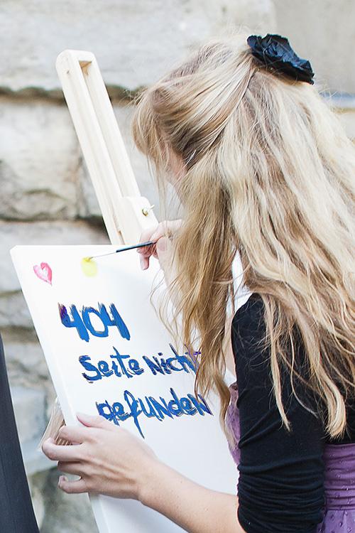 Eine Frau malt bei einer Hochzeit eine 404-Meldung an einer Staffelei.
